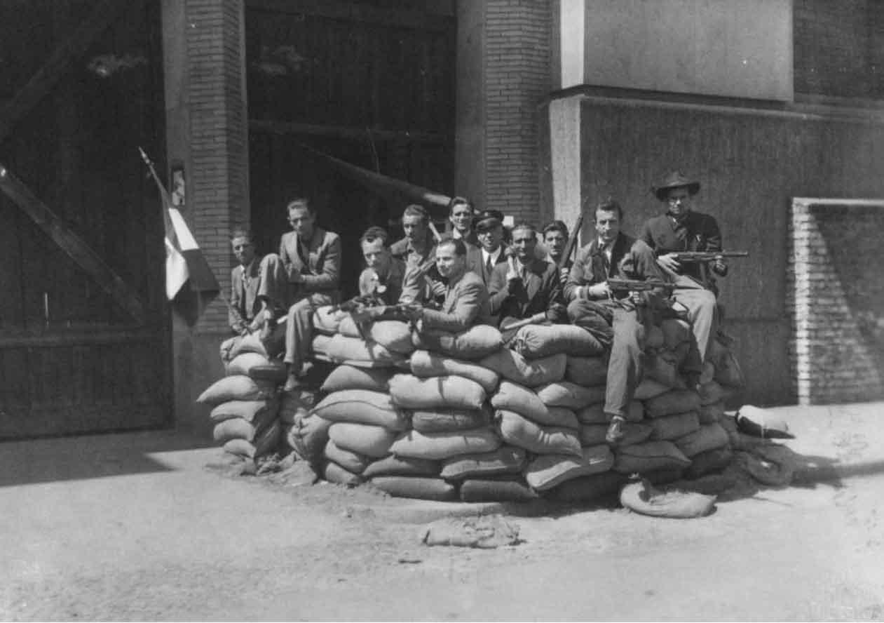 I partigiani con i loro fucili posano per il fotografo nella postazione di via Ceresio, eretta a difesa della centrale termoelettrica, Milano